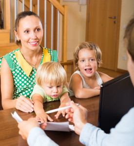 Happy mother with two playful children glad hearing words of social worker at home